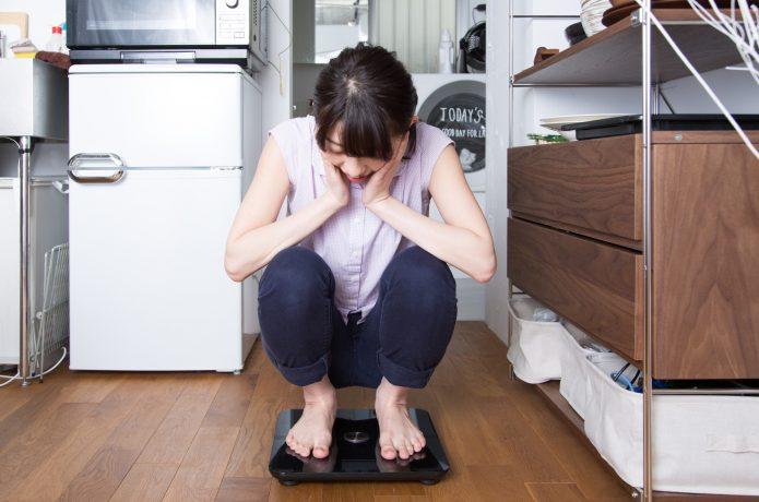 体重計に乗って驚いている女性