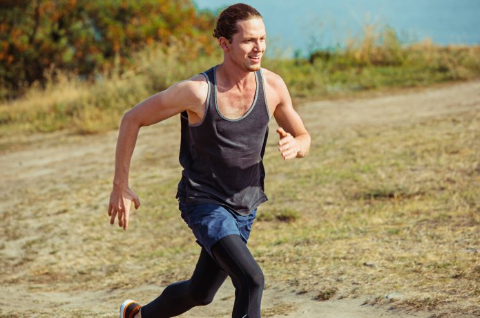 自然の中の登り坂を走る男性