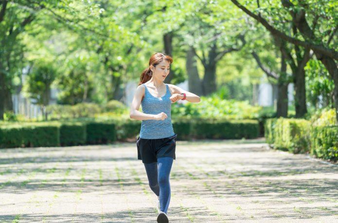 時間をチェックしながら走る女性