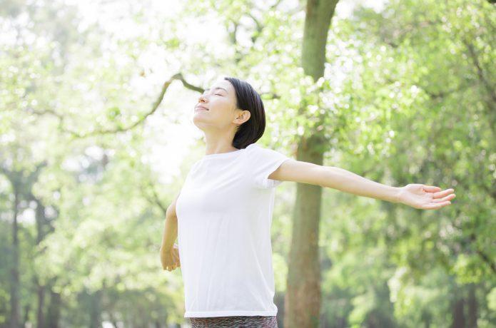 朝の公園で深呼吸をする女性ランナー