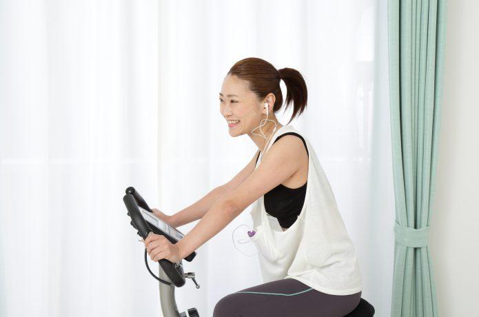 正しい姿勢でエアロバイクに乗る女性