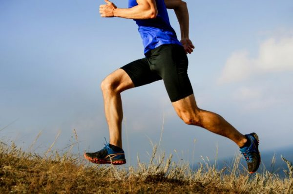 足の筋肉を収縮させて走る男性