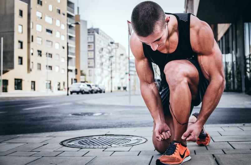 靴ひもを結ぶ筋肉質な男性