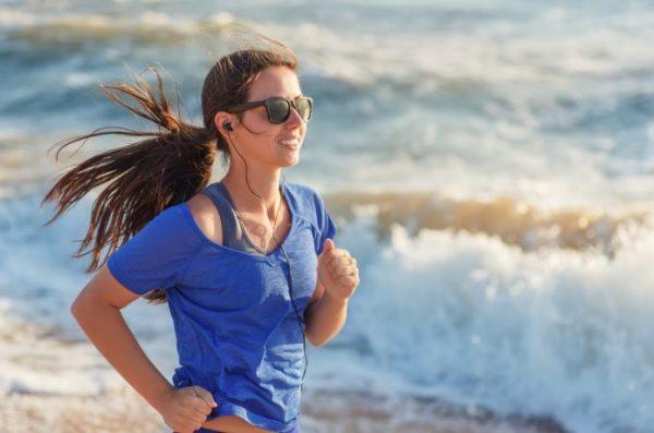 サングラスをかけて海辺を走る女性