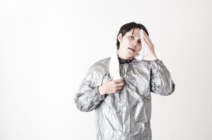 サウナスーツを着て汗をふく男性