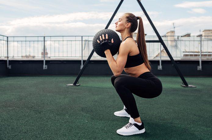 メディシンボール を持ってスクワットをする女性