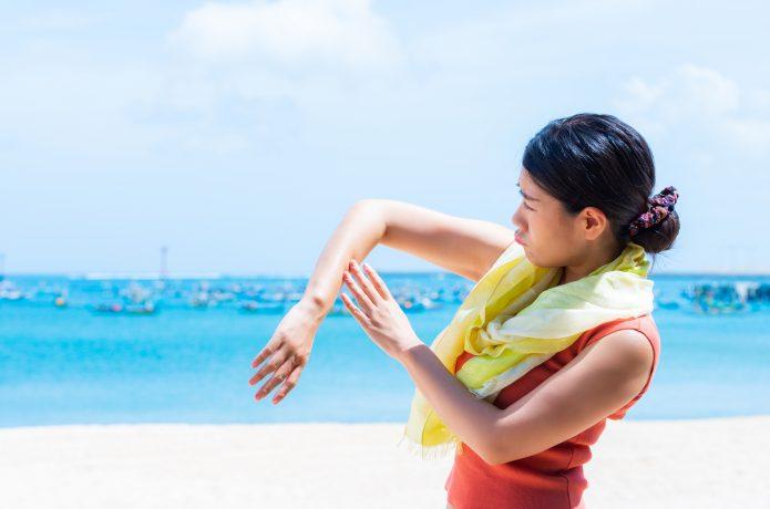海辺で日焼けを心配する女性