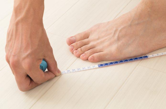 足のサイズを計測する男性