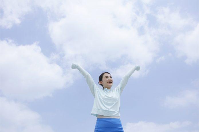 青空の下で笑顔の女性