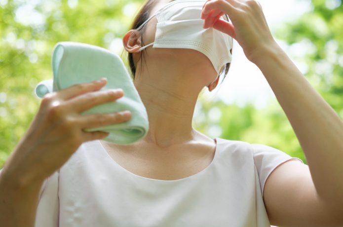 マスクをして暑がる女性