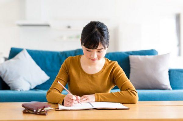 家で書き物をする女性