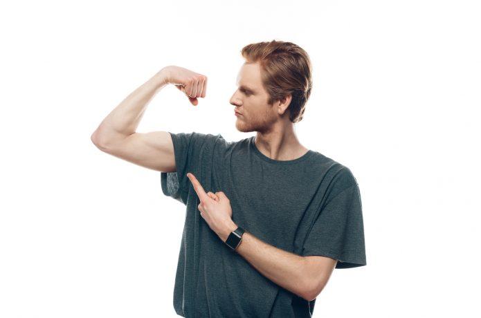 腕の筋肉を指で指し示す男性