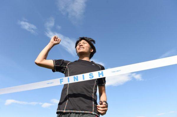 マラソンのゴールテープを切る男性ランナー