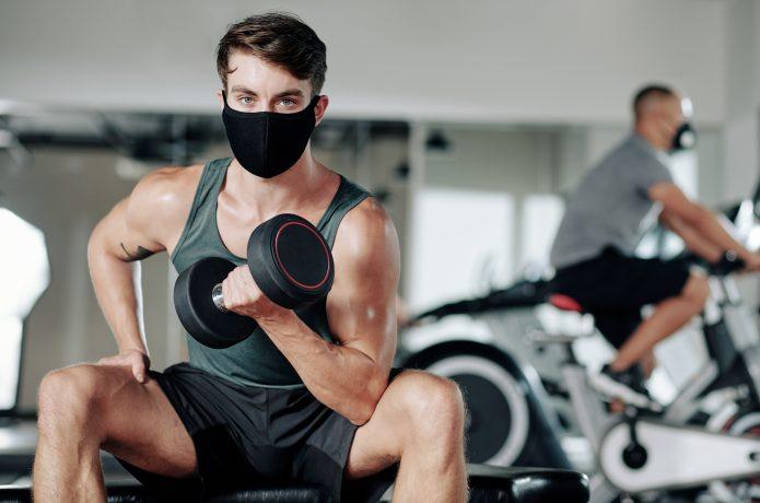 ジムでマスクをしながらトレーニングする男性
