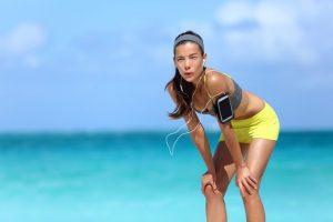 海辺で呼吸を整える女性ランナー
