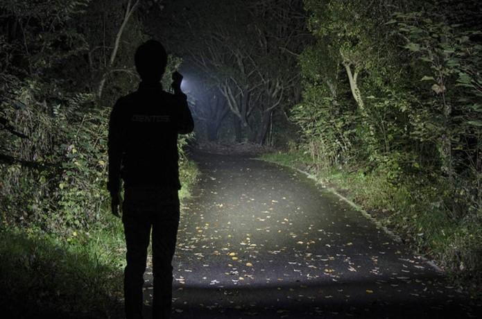 ハンディライトで前方を照らしている人