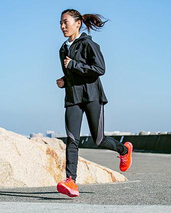 ウインドブレーカーを着て走る女性