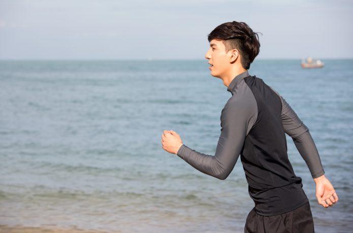 海辺をランニングをする男性の画像
