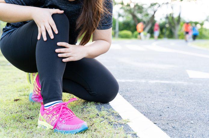 足を痛めているランニング中の女性