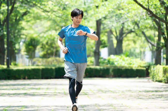 時間を確認しながら走る男性